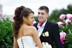 Happy bride and groom near peony flowers Royalty Free Stock Images