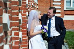 Happy bride and groom near red brick wall Stock Images