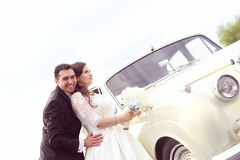 Happy bride and groom near retro car Stock Images