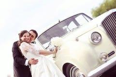 Happy bride and groom near retro car Royalty Free Stock Photos