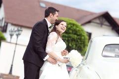 Happy bride and groom near retro car Stock Photos