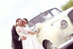 Happy bride and groom near retro car Stock Images