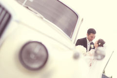 Happy bride and groom near retro car Stock Photography