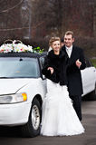 Happy bride and groom near wedding limo Stock Photos