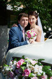 Happy bride and groom near wedding limo Stock Photo