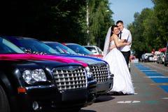 Happy bride and groom near wedding limousines. On romantic walk Royalty Free Stock Image