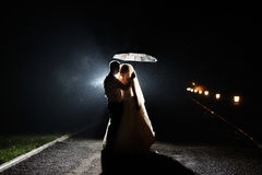 Happy bride and groom night with umbrella Royalty Free Stock Photo