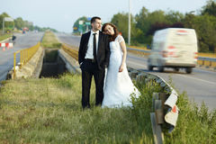 Happy bride and groom outside the city on the road. Royalty Free Stock Photo