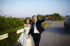 Happy bride and groom outside the city on the road. Stock Photography
