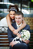 Happy bride and groom on park bench Stock Images