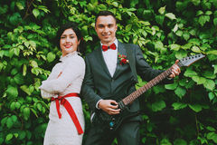Happy bride and groom playing the guitar Stock Images