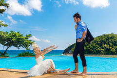 Happy bride and groom poolside infinity. Tropical sea in the bac Royalty Free Stock Images