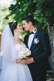 Happy bride and groom posing in a park Royalty Free Stock Image
