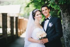 Happy bride and groom posing in a park Stock Photo