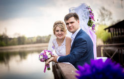 Happy bride and groom posing on pier at lake Royalty Free Stock Photography