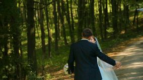 Happy bride and groom pretty girl hugging and kissing in the forest stock footage