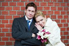 Happy bride and groom on red brick wall Royalty Free Stock Photography