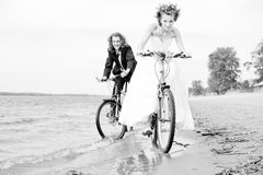 Happy bride and groom rides on bicycles. B&W photo of Happy bride and groom rides on bicycles stock images