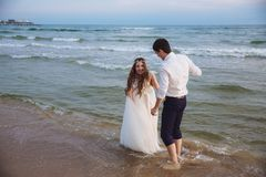 Happy bride and groom run along ocean shore. Newlyweds having fun at wedding day on tropical beach royalty free stock photography