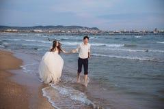 Happy bride and groom run along ocean shore. Newlyweds having fun at wedding day on tropical beach stock photos