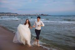 Happy bride and groom run along ocean shore. Newlyweds having fun at wedding day on tropical beach royalty free stock image