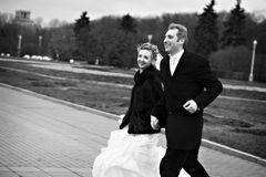 Happy bride and groom run on garden Royalty Free Stock Photography
