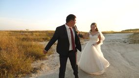 Happy bride and groom run on white road. Couple in love runs hand in hand on a summer evening in park. Happy family stock footage