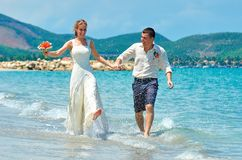 Happy Bride and groom running on a beautiful tropical beach Stock Image