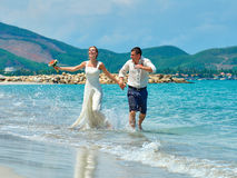 Happy Bride and groom running on a beautiful tropical beach Stock Images