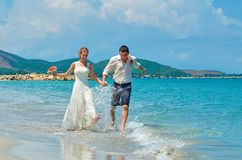 Happy Bride and groom running on a beautiful tropical beach Royalty Free Stock Images