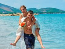 Happy Bride and groom running on a beautiful tropical beach stock photography