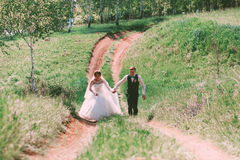 Happy bride and groom running on road Stock Photography