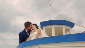 Happy bride with groom sailing on the ship. Under the helm of the young man stock video