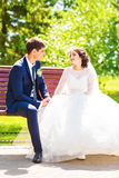Happy bride and groom sit on the bench Stock Photography