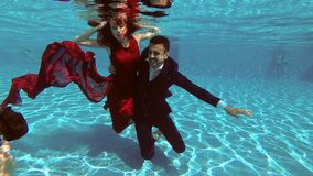 Happy bride and groom sit under the water at the bottom of the pool, smiling and looking at the photographer who takes stock video