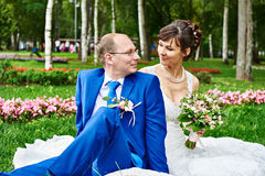 Happy bride and groom sitting on grass at wedding walk Royalty Free Stock Photos