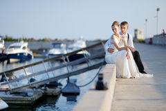 Happy bride and groom sitting on pier Royalty Free Stock Images