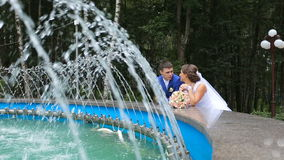 Happy bride and groom standing near the fountain. Newlyweds, the bride and groom are standing around the fountain and talk. Loving wedding couple outdoor. Bride stock video