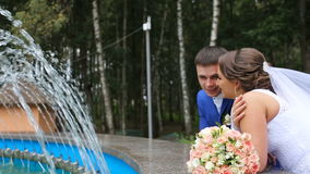 Happy bride and groom standing near the fountain in the park. Newlyweds, the bride and groom around the fountain and talk. Loving wedding couple outdoor. Bride stock video