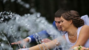 Happy bride and groom standing near the fountain in the park. Bride and groom play with water jets Fountain. Loving wedding couple outdoor. Bride and groom stock video