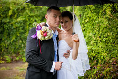 Happy bride and groom standing under umbrella Stock Images