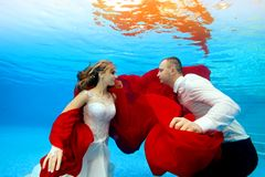 Happy bride and groom swim underwater at sunset. They look at each other and smile with a red cloth in their hands on a blue. Background. Portrait. Concept royalty free stock photo