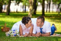 Happy bride and groom on their wedding lies on the grass in park Royalty Free Stock Photos