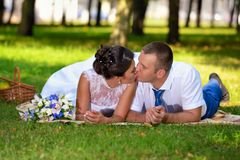 Happy bride and groom on their wedding lies on the grass in park and kiss royalty free stock images