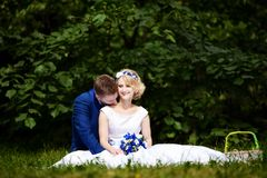 Happy bride and groom on their wedding sits on grass in park Stock Photos