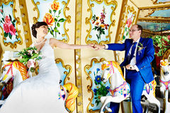 Happy Bride and groom on toys horses fun fair at wedding walk Stock Photo