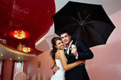 Happy bride and groom with umbrella Stock Photography