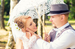 Happy bride and groom with umbrella in a forest Stock Image