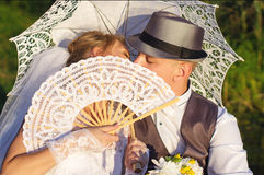 Happy bride and groom with umbrella Stock Image
