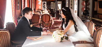 Happy bride and groom in vintage interior of resrourant Royalty Free Stock Image
